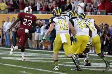 "Bruce finishes ""The Drive"" as three Michigan defenders look on."